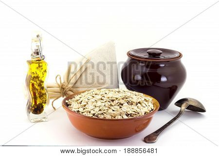 Still life of Porridge oate in ceramic pial, ceramic pot, old spoon and canvas bag for cereals, oil with spices and seasonings, isolated on white background
