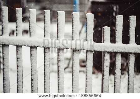 Old wooden fence covered with snow. The broken part.