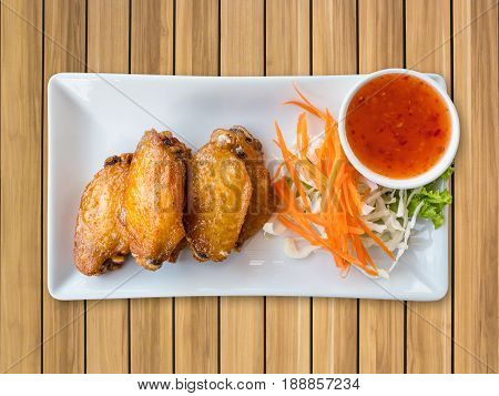 chicken wings with hot spicy barbecue sauce on wood background.