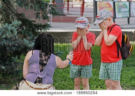 Volgograd Russia - June 01 2014: Mother spraying insect repellents on children with spray bottle in Volgograd