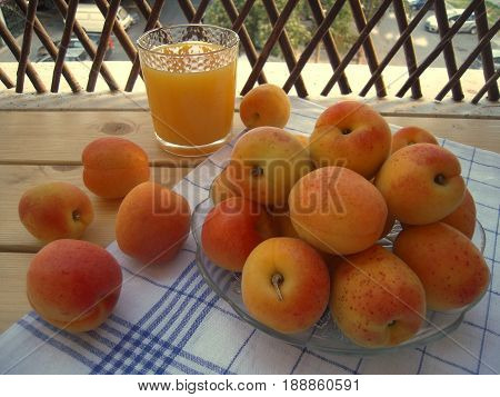 Apricots on a plate and a glass of juice on a wooden table on the veranda.