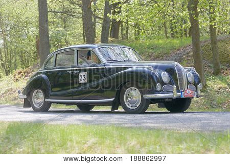STOCKHOLM SWEDEN - MAY 22 2017: Black BMW 3.3 V8 classic car from 1962 driving on a country road in the public race Gardesloppet in the forests at Djurgarden Stockholm Sweden. May 22 2017