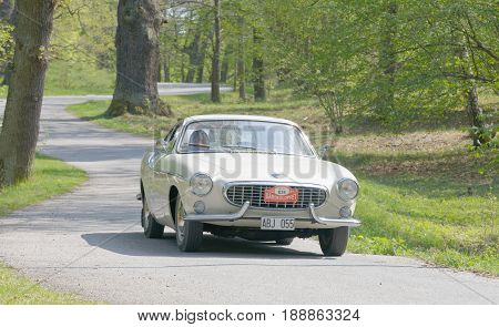 STOCKHOLM SWEDEN - MAY 22 2017: White Volvo P1800 S classic car from 1963 driving on a country road in the public race Gardesloppet in the forests at Djurgarden Stockholm Sweden. May 22 2017