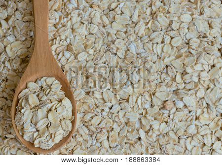 Oat flakes or oatmeal in wood spoon on rustic wood table. Rolled oat is clean food for health lover people. Prepare oat flakes for bakery or cooking.Natural organic food in vintage style concept.Oat flake, oatmeal background and texture.