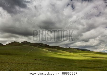 Green hills with cloudy sky. Mongolian steppe
