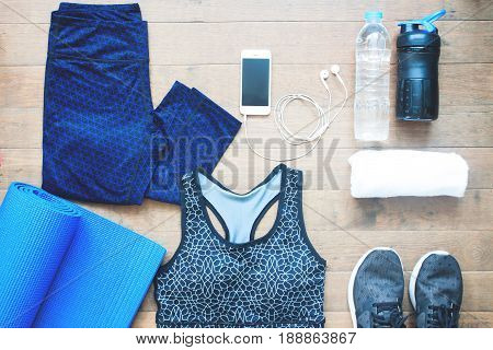 Sport equipments. Sport bra. Smartphone and sport shoes on wood floor Healthy lifestyle concept