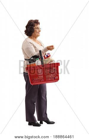 Full length profile shot of an elderly woman with a shopping basket waiting in line isolated on white background