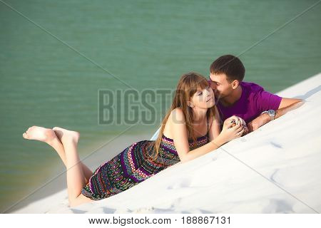 Lovers lying and kissing on the barkhan. romantic travel honeymoon vacation summer holidays. young girl dressed in a colorful dress and man in a violet t-shirt. they embracing outdoors