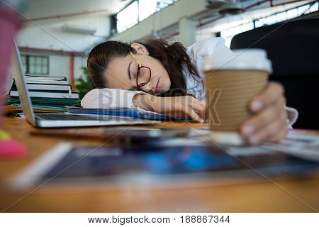 Tired female graphic designer holding disposable cup while sleeping on desk in office