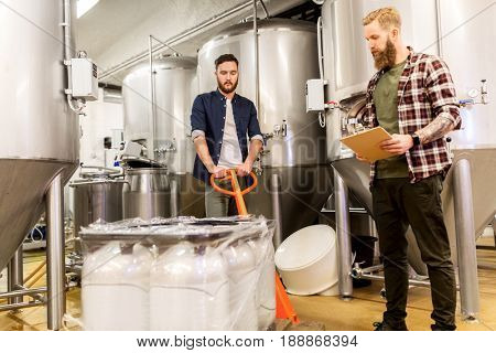 manufacture, business and people concept - men with malt bags on loader and clipboard working at craft brewery or beer plant