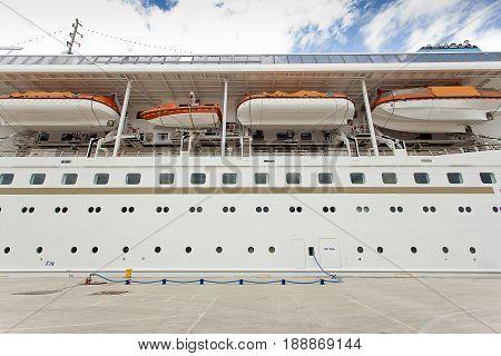 Luxury Cruise Ship Sailing from Port at dusk