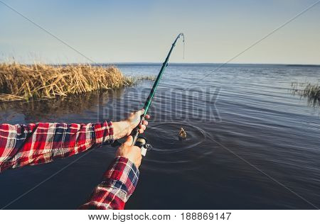 The Fisherman Catches Fish On The Shore Of The Lake, Holds His Hands Spinning Against The Beautiful