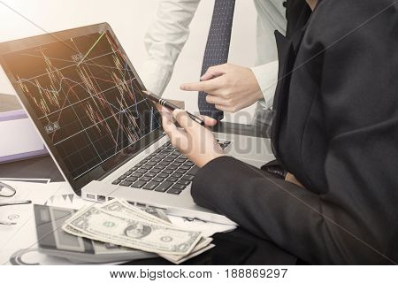 business hand point on a laptop with Stock trade graph homepage on the computer screen finance and banking website web page concept.