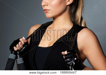 sport, fitness and people concept - close up of young sporty woman with jumping rope