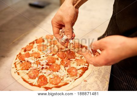 food, culinary, italian cuisine, people and cooking concept - cook hands adding ham to salami pizza at pizzeria