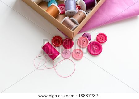 needlework, craft, sewing and tailoring concept - box with thread spools and buttons on table