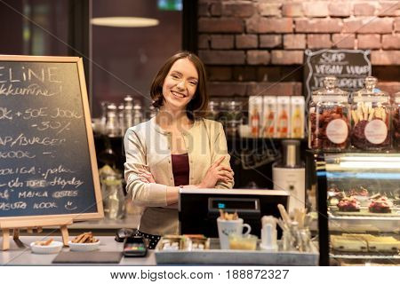 small business, people and service concept - happy woman or barmaid at counter with cashbox in cafe or coffee shop