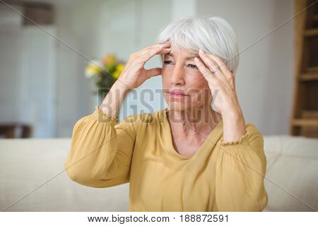 Senior woman suffering from head ache in living room at home