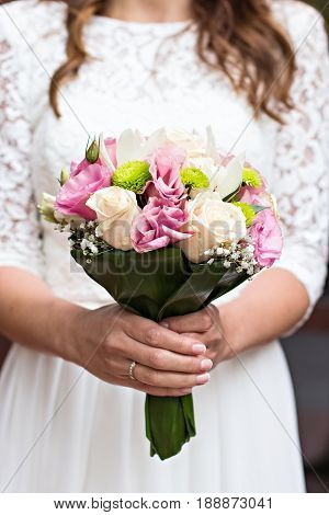 A Bride's Bouquet In Female Hands.