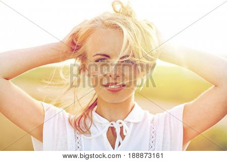 happiness, country, summer holidays, vacation and people concept - close up of happy smiling young woman or teenage girl with wild hair outdoors
