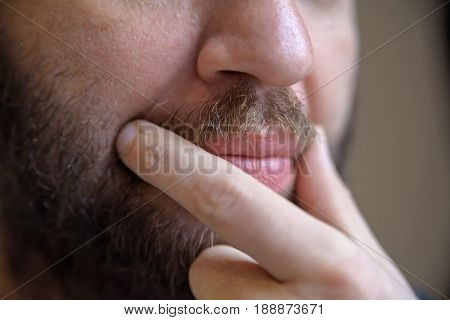 Close-up of young handsome bearded man touching his moustache with two fingers thinking