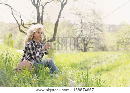 Beautiful blonde is drinking coffee in the park