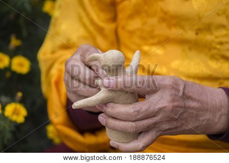 Tibetan monk sculpted figure of the deity of barley flour tsampa for Buddhist religious ceremony in Nepal. Close up