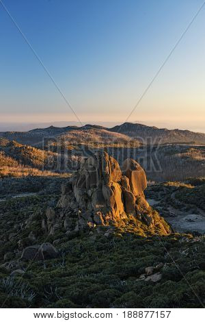 Sunrise as viewed atop a hiking trail known as `The Hump` in Mt Buffalo National Park in the Victoria Australia alpine region. The rock formation is known as `The Cathedral`