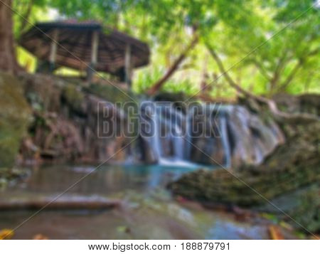 Abstract blurred waterside pavilion with small waterfall.