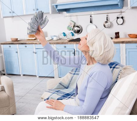 Elderly woman holding large amount of money in her hands. Elderly woman holding much money in her hands while sitting on sofa or couch.