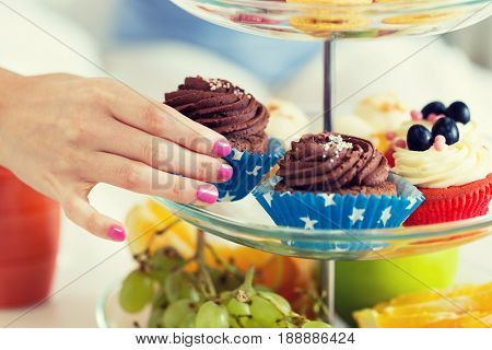 people, unhealthy eating and junk food concept - close up of hand taking cupcake from cake stand