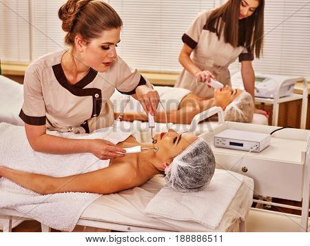 Couple facial massage beauty salon. Electric stimulation woman and man skin care . Equipment microcurrent lift face for family . Anti aging rejuvenation and non surgical treatment for group people.