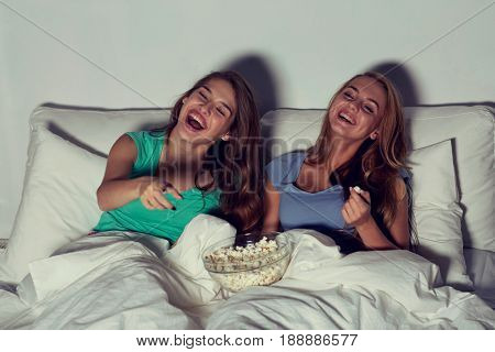 friendship, people, pajama party, entertainment and junk food concept - happy friends or teenage girls eating popcorn and watching movie or tv series at home