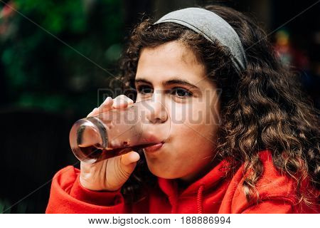 Girl drinking a refreshing glass of cola in a bar