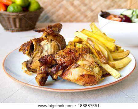 Pollo asado con patatas y ensalada. Roasted chicken with potatoes and salad.