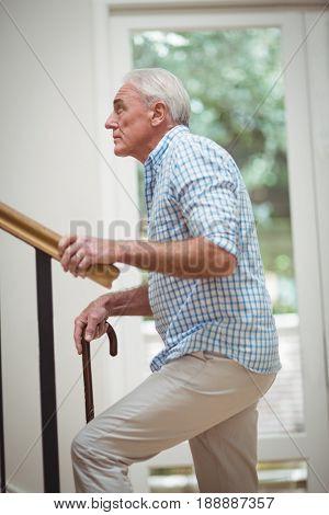 Senior man climbing upstairs with walking stick at home