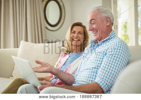 Senior couple interacting with each other while using laptop in living room at home poster
