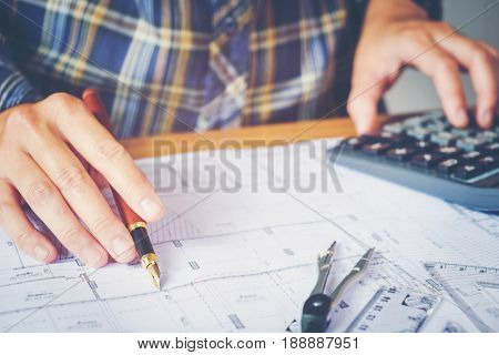 Architect or engineer working in office on blueprint. Architects workplace blueprints ruler helmet and divider. Construction concept. Engineering tools