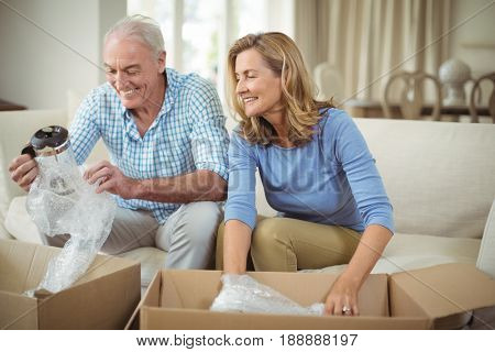 Smiling senior couple unpacking carton boxes in living room at new home