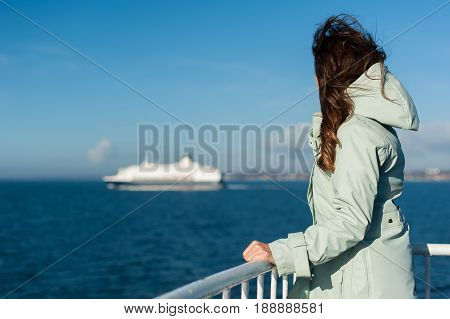 Young traveller woman sailing a ferry, with big boat cruise liner or ferry on the background, wearing a rain jacket.