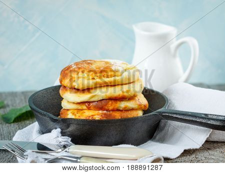 Homemade cottage cheese pancakes in a cast-iron frying pan. Russian dessert from cottage cheese.