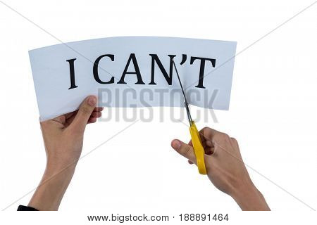 Conceptual image of businesswoman cutting a paper that reads we cant against white background