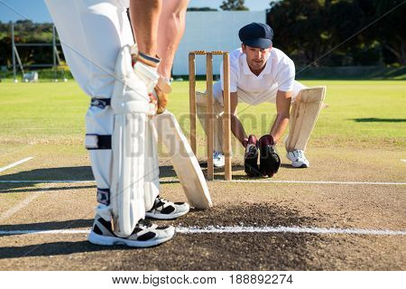 Close up of man batting while playying cricket at field on sunny day