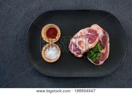 Sirloin chops, salt and spices against black background