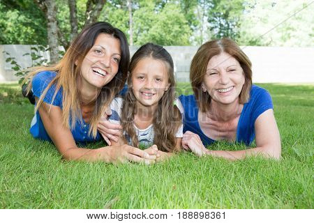 Three Generations Of Women Are Lying In The Green Grass Garden Park
