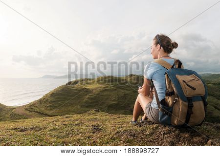 Hiker woman with backpack relax and enjoying sunset on peak of hill. Traveling along mountains and coast freedom and active lifestyle concept.