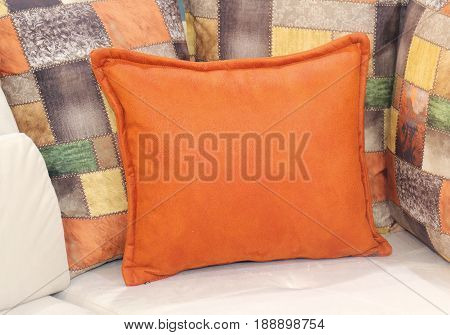 Soft orange decorative pillow with more pillows in the back