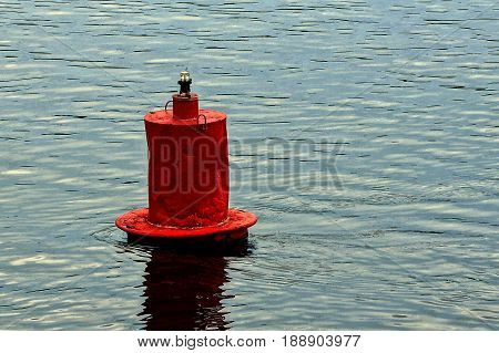 Red iron buoy in the water of the river