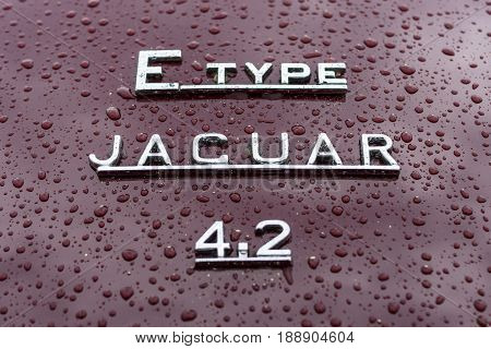 BERLIN - MAY 13 2017: Emblem of the sports car Jaguar E-Type in raindrops on the burgundy background. Exhibition