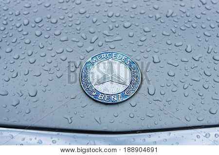 BERLIN - MAY 13 2017: Hood emblem of Mercedes-Benz in raindrops on the gray background. Exhibition